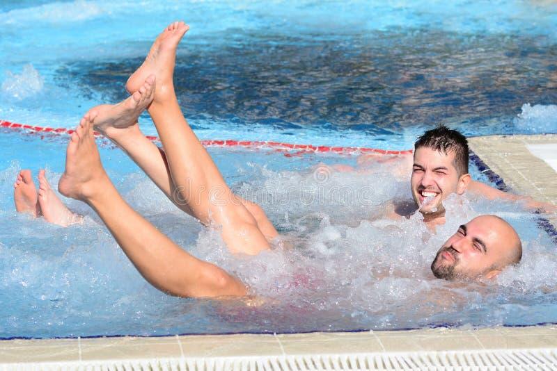 Dos hombres que disfrutan del baño de burbujas de la tina caliente del Jacuzzi al aire libre imagen de archivo