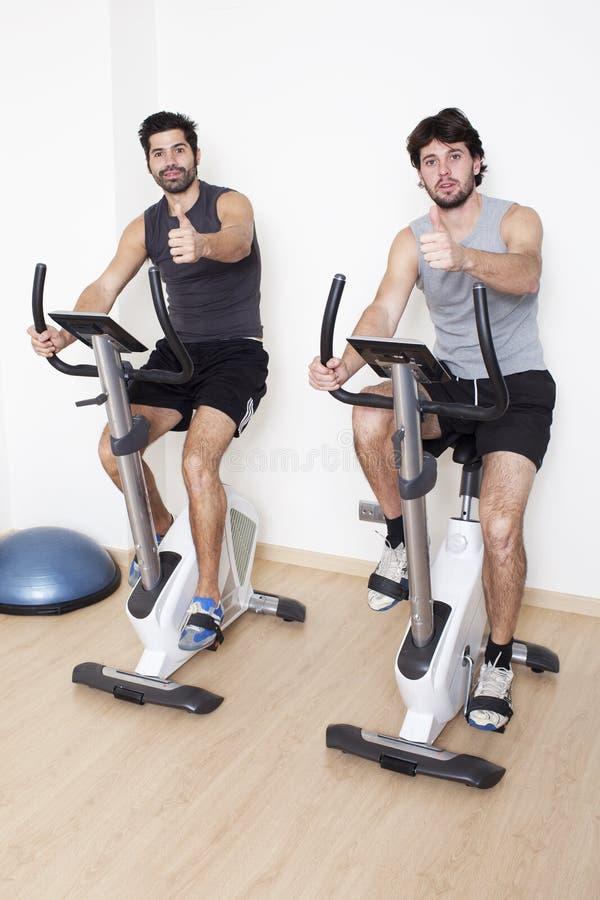 Dos hombres que hacen girar con los pulgares para arriba imagenes de archivo