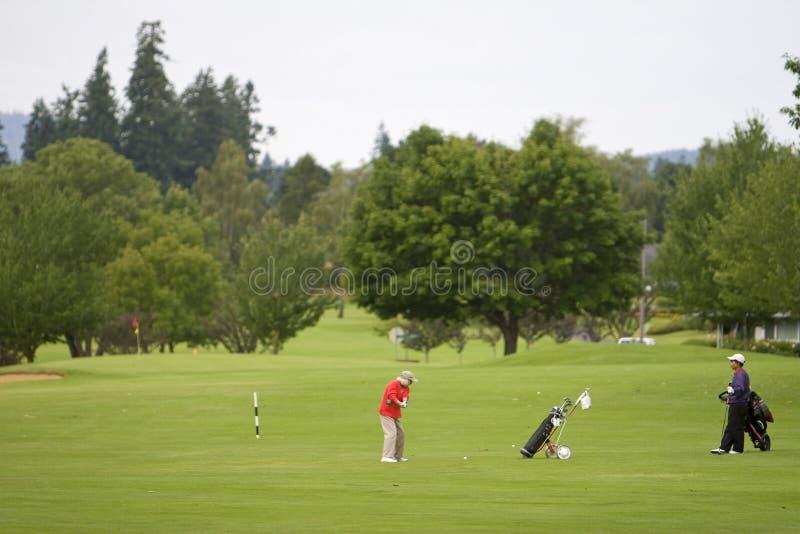 Dos hombres que juegan al golf - horizontal imágenes de archivo libres de regalías