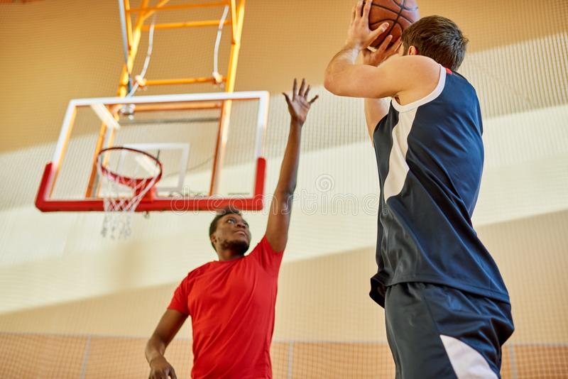 Dos hombres que juegan a baloncesto en gimnasio fotos de archivo libres de regalías