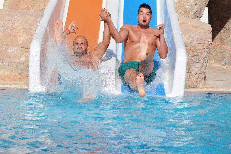 Dos hombres que montan abajo de los diapositiva-amigos de un agua que gozan de un tubo del agua montan imágenes de archivo libres de regalías