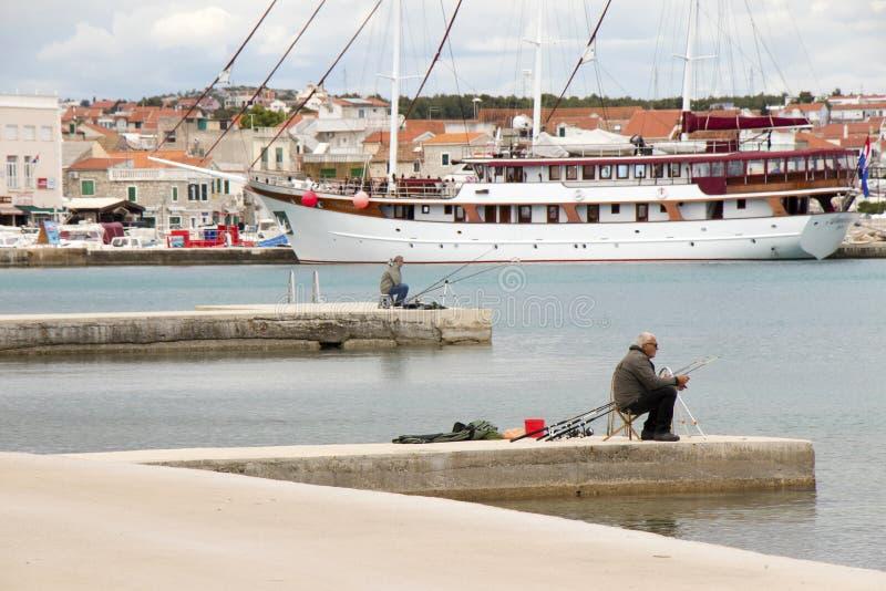 Dos hombres que pescan en un embarcadero de la playa, un velero detrás de ellos con la vista panorámica de la ciudad foto de archivo