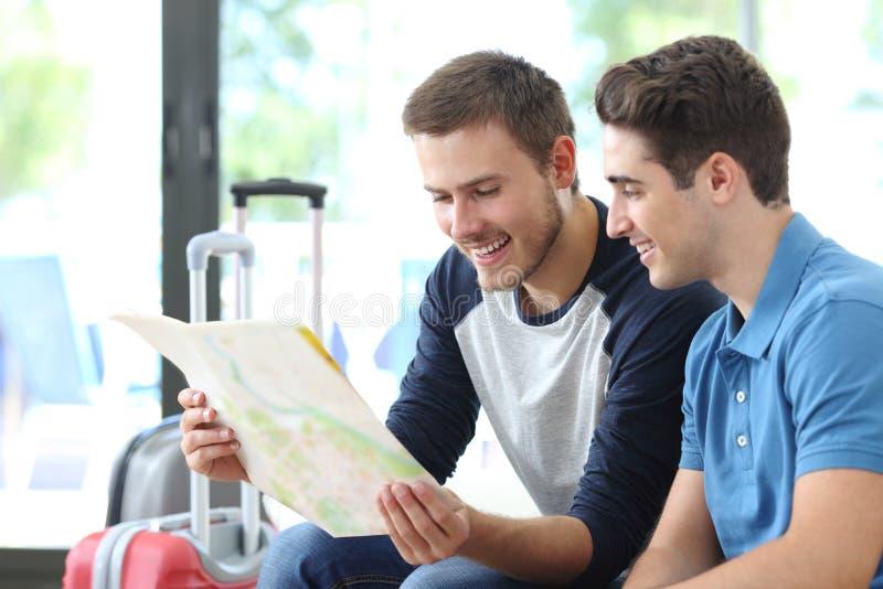 Dos hombres que planean las vacaciones que comprueban el mapa fotos de archivo