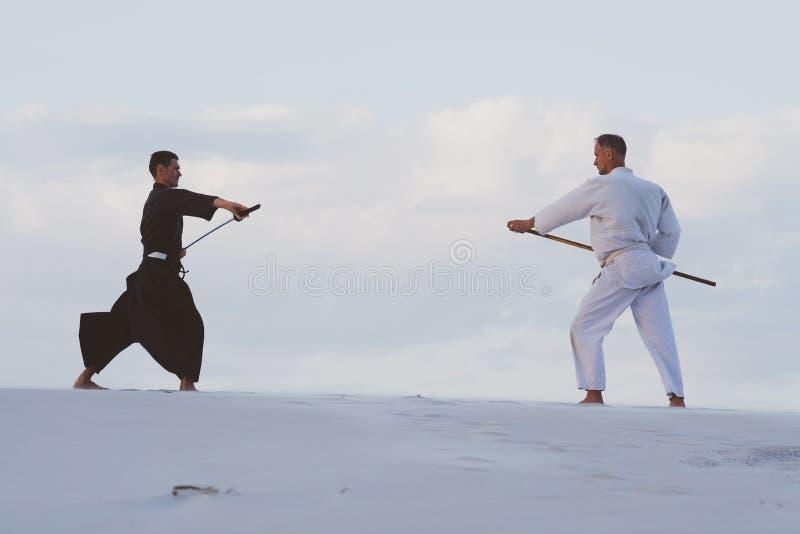 Dos hombres que practican artes marciales japoneses en desierto imágenes de archivo libres de regalías
