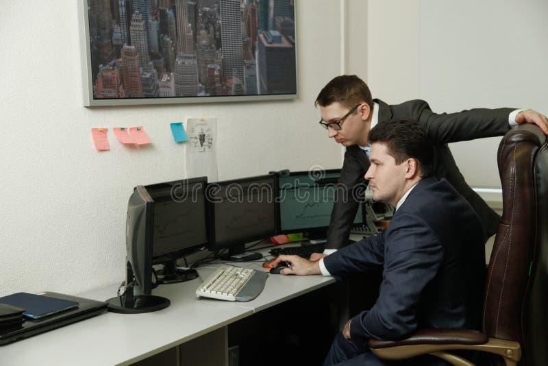 Dos hombres que trabajaban juntos para los ordenadores en la oficina engancharon al comercio imagen de archivo