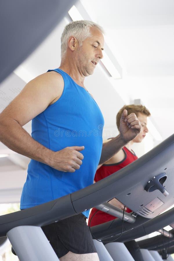 Dos hombres que usan las máquinas corrientes en gimnasio imagen de archivo libre de regalías
