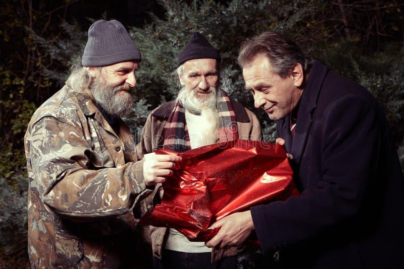 Dos hombres sin hogar que recompensan al hombre en el traje para el regalo de la comida en tiempo de la Navidad foto de archivo libre de regalías