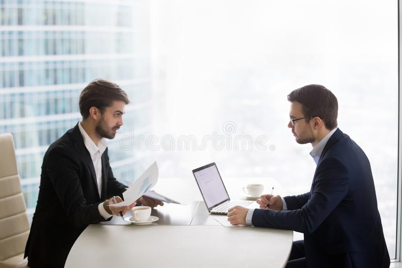 Dos hombres son que hablan y de trabajos con los papeles en oficina imagen de archivo