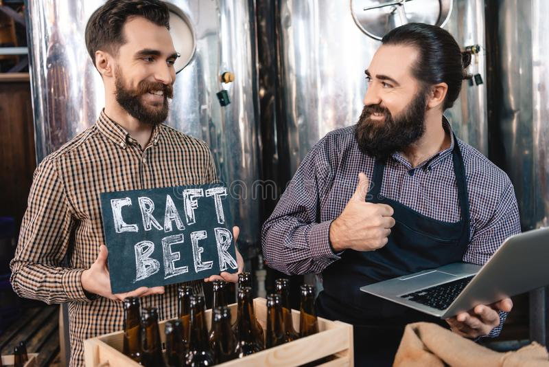 Dos hombres sonrientes muestran a muestra donde se escribe la cerveza del arte Producción de cerveza del arte imagenes de archivo