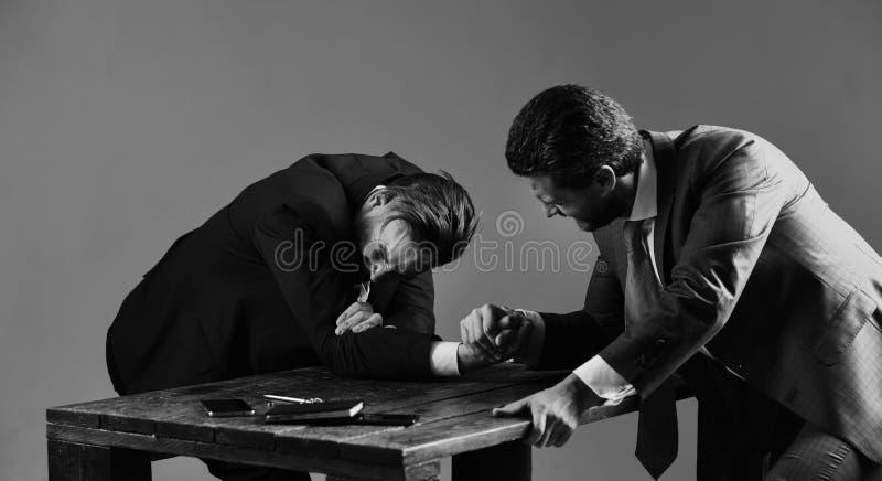 Dos hombres u hombres de negocios que luchan con los brazos, lucha para la dirección fotografía de archivo libre de regalías