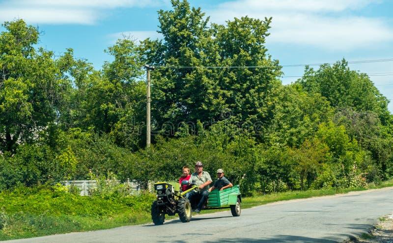 Dos hombres y un paseo del muchacho un minitractor en el camino en el campo foto de archivo
