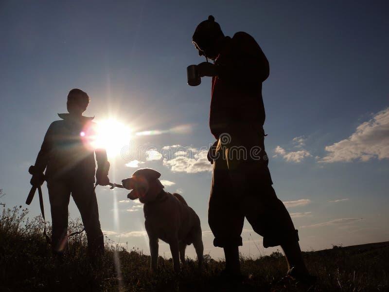 Dos hombres y un perro en la puesta del sol fotos de archivo