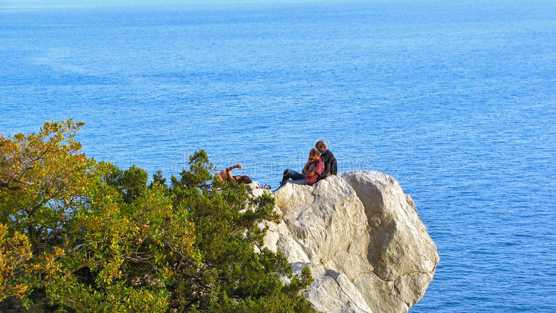 Dos hombres y una mujer que descansa sobre una repisa de la roca sobre el mar imagen de archivo libre de regalías