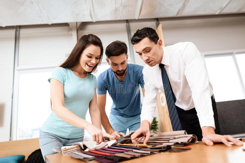 Dos hombres y una mujer que se coloca sobre las muestras de la tapicería para los muebles fotos de archivo