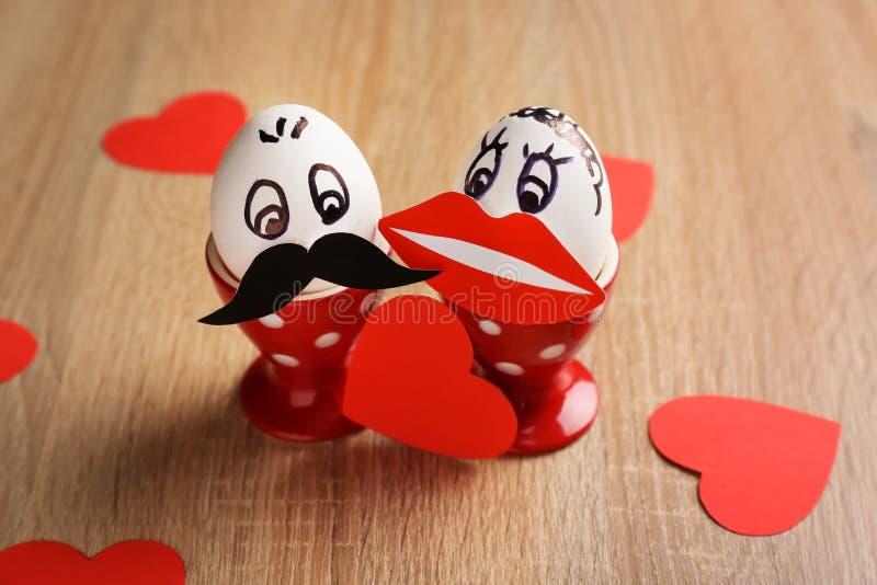 Dos huevos divertidos con los corazones en la tabla de madera imagenes de archivo