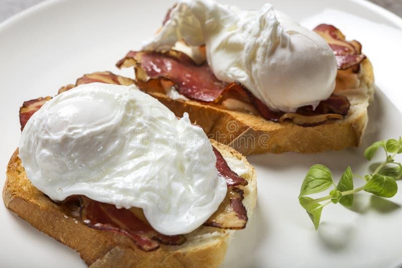 Dos huevos escalfados con tocino en tostada cocinaron el desayuno imágenes de archivo libres de regalías