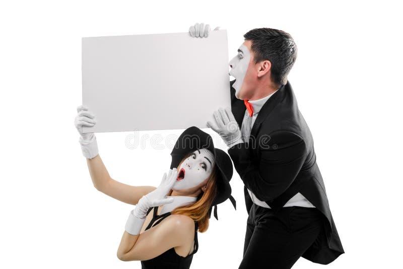 Dos imita llevando a cabo el cartel en blanco imagen de archivo libre de regalías