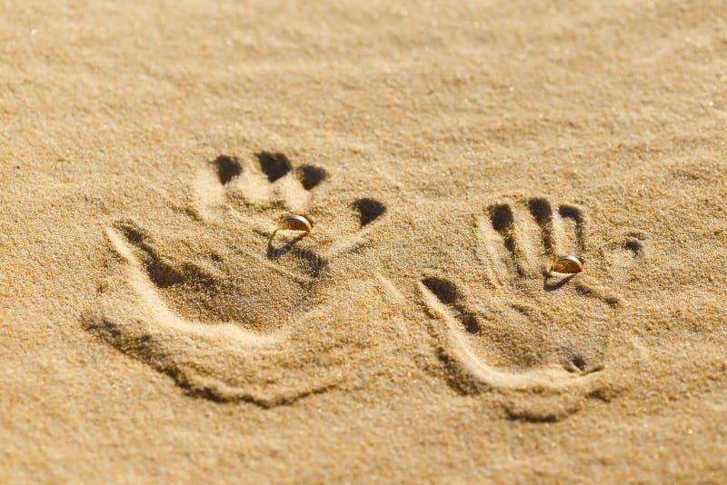 Dos impresiones de la palma en la arena con los anillos de bodas fotos de archivo libres de regalías