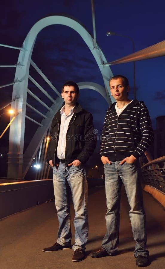 Dos individuos en el puente de la noche imágenes de archivo libres de regalías