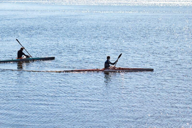 Dos individuos en wetsuits en un flotador del kajak imagenes de archivo