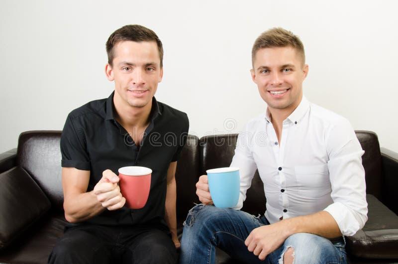 Dos individuos felices están bebiendo el café foto de archivo