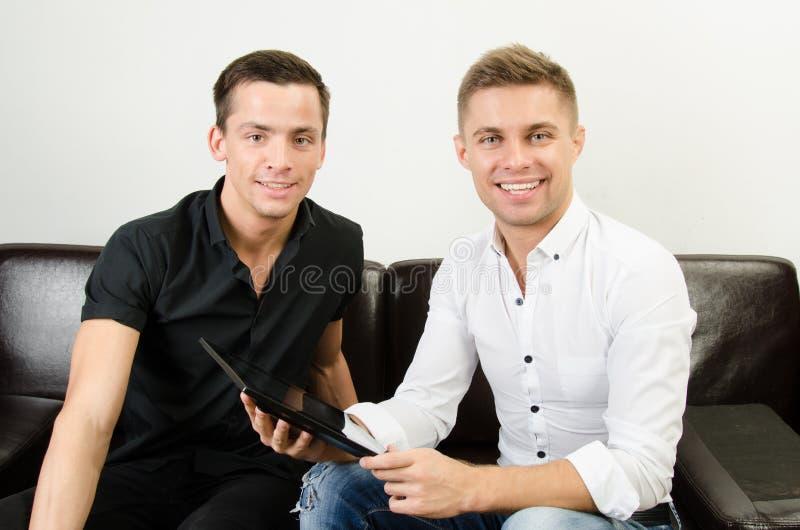 Dos individuos felices están trabajando en una tableta fotos de archivo