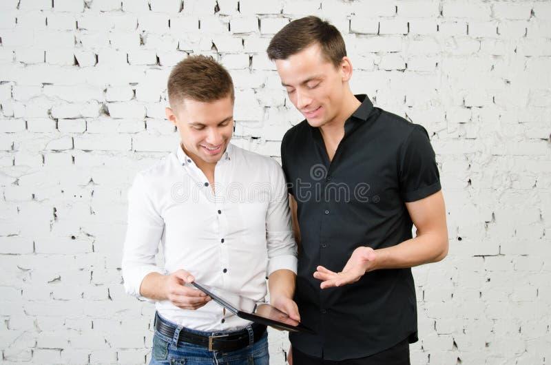 Dos individuos felices y una tableta Trabajo y estudio fotos de archivo libres de regalías