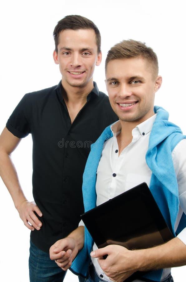 Dos individuos felices y una tableta Trabajo y estudio Fondo blanco fotos de archivo libres de regalías