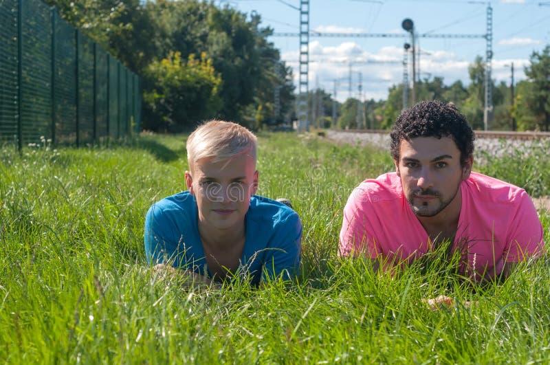 Dos individuos jovenes hermosos en la hierba fotografía de archivo