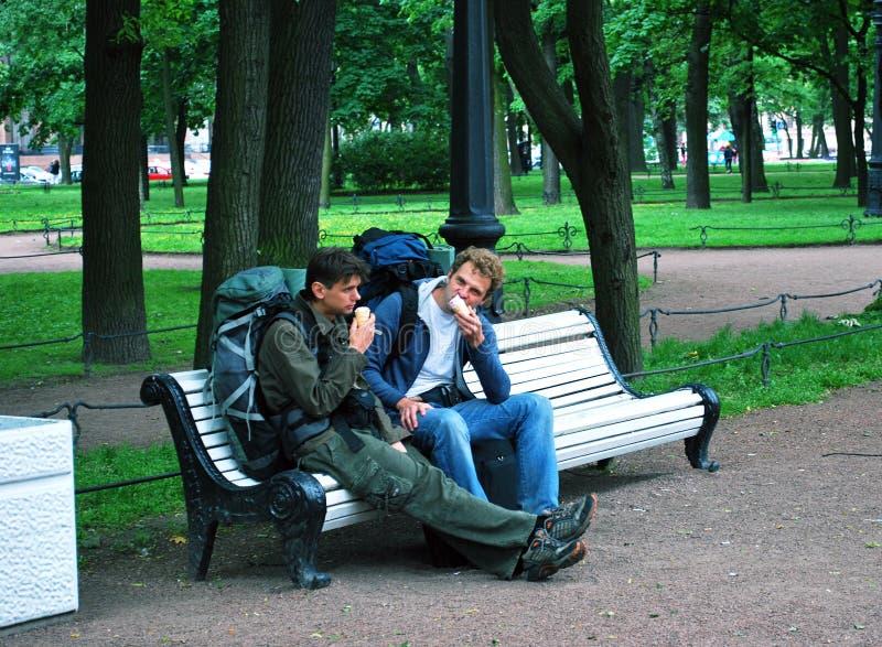 Dos individuos jovenes, turistas, sentándose en un banco en parque comen el hielo-cre imagen de archivo