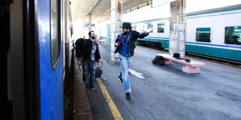 Dos individuos son atrasados para que el tren y el funcionamiento lo cojan Uno de ellos se pierde fotografía de archivo libre de regalías