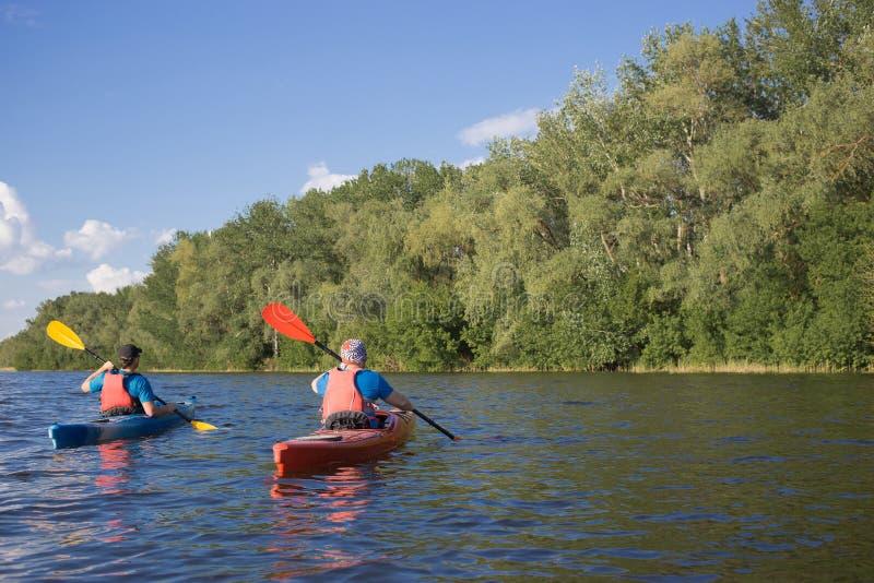 Dos individuos viajan el río en kayaking fotos de archivo libres de regalías
