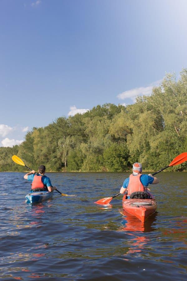 Dos individuos viajan el río en kayaking foto de archivo