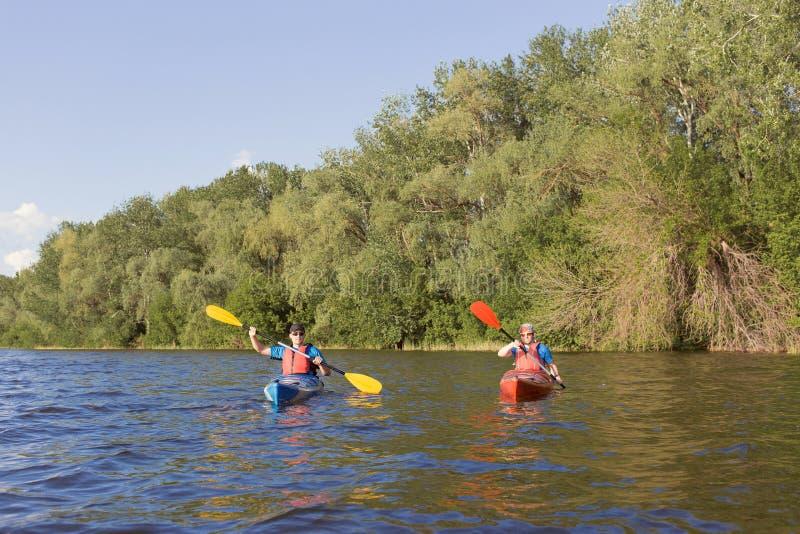 Dos individuos viajan el río en kayaking imágenes de archivo libres de regalías