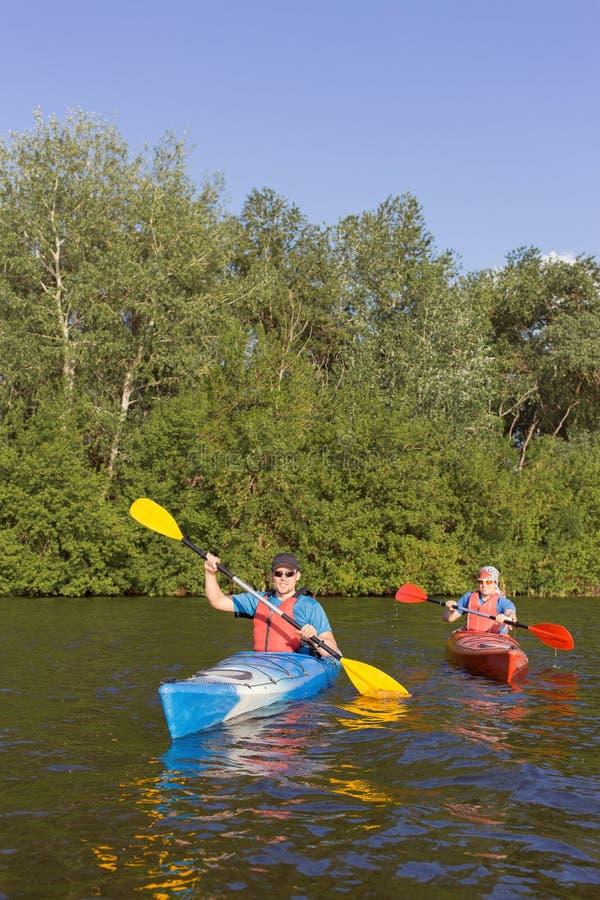 Dos individuos viajan el río en kayaking fotografía de archivo