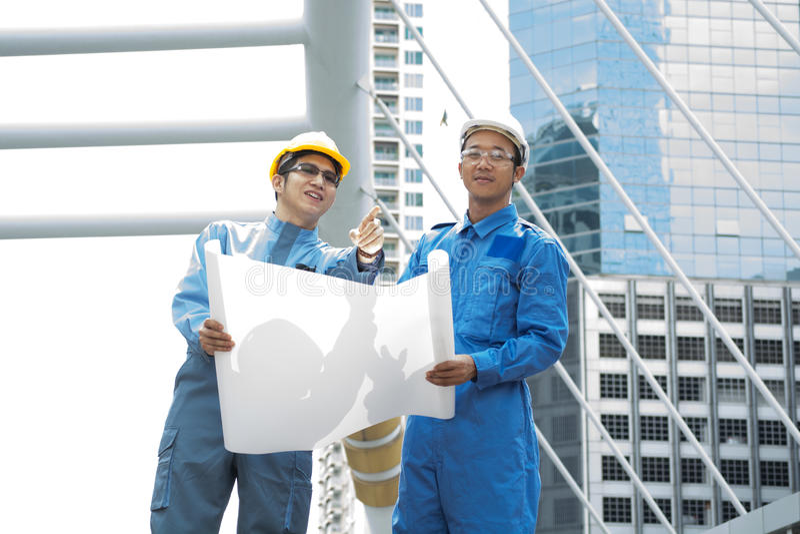 Dos ingeniero o arquitecto discuten en proyecto de edificio moderno en fotos de archivo