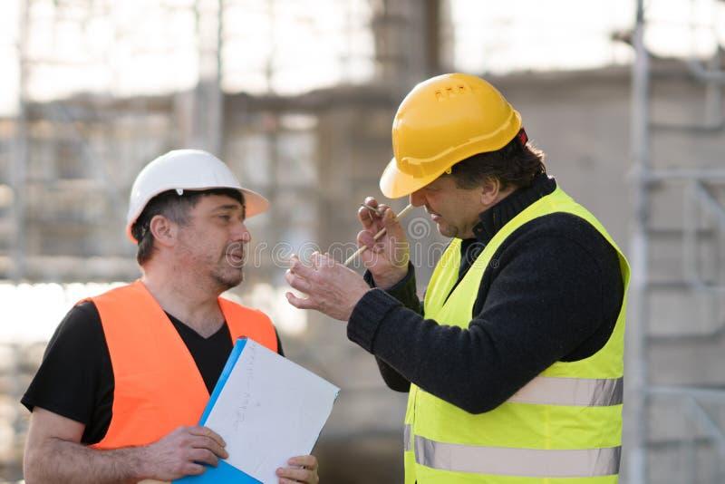 Dos ingenieros civiles de sexo masculino en el trabajo imagen de archivo