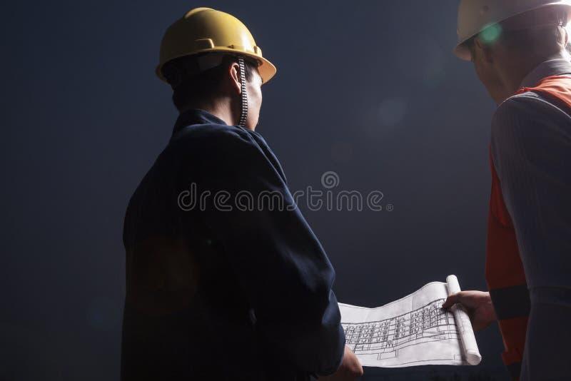 Dos ingenieros de sexo masculino jovenes en los cascos de protección que miran abajo un modelo la oscuridad, vista posterior imagen de archivo libre de regalías