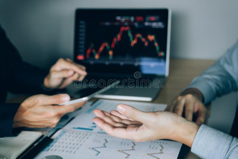 Dos inversores están trabajando así como analizar los gráficos comunes de los datos en el papel y la visión de los datos foto de archivo libre de regalías