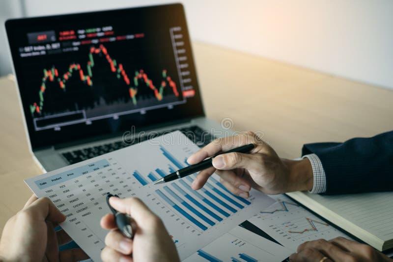 Dos inversores est?n trabajando as? como analizar los gr?ficos comunes de los datos en el papel y la visi?n de los datos sobre la foto de archivo libre de regalías