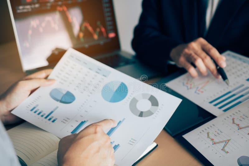 Dos inversores est?n trabajando as? como analizar los gr?ficos comunes de los datos en el papel y la visi?n de los datos sobre la fotografía de archivo