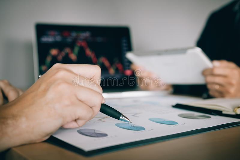 Dos inversores est?n trabajando as? como analizar los gr?ficos comunes de los datos en el papel y la visi?n de los datos sobre la fotos de archivo libres de regalías