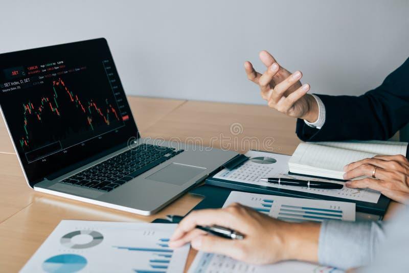 Dos inversores que trabajan juntos están analizando la carta común en la pantalla de ordenador en la compañía foto de archivo