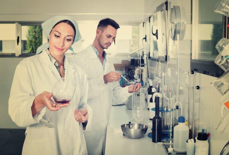 Dos investigadores en la capa blanca que comprueban acidez del vino en laborator foto de archivo libre de regalías