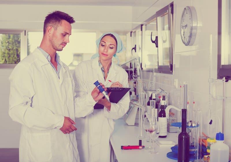 Dos investigadores en la capa blanca que comprueban acidez del vino en laborator fotografía de archivo libre de regalías