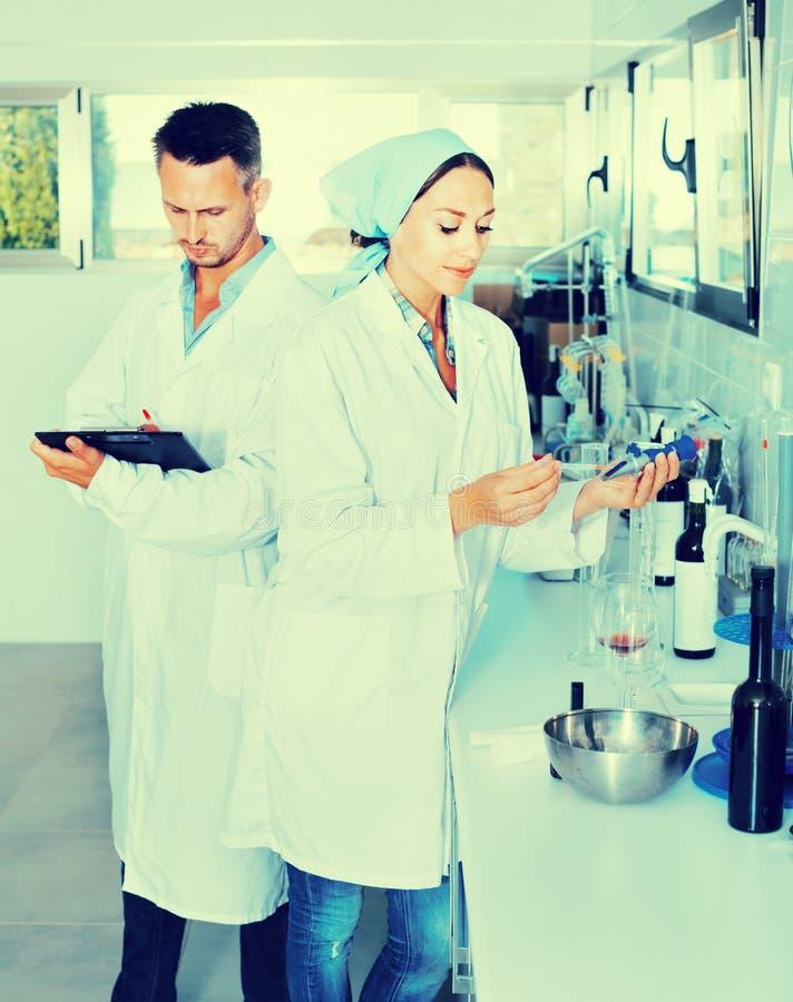 Dos investigadores en la capa blanca que comprueban acidez del vino en laborator imagen de archivo