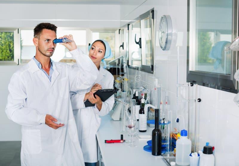 Dos investigadores en la capa blanca que comprueban acidez del vino en laboratorio foto de archivo