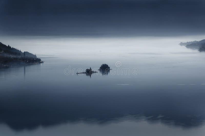 Dos islas cerca de Perast en la bahía de Kotor en la madrugada en la niebla 2019-02-17 08: 38 foto de archivo libre de regalías
