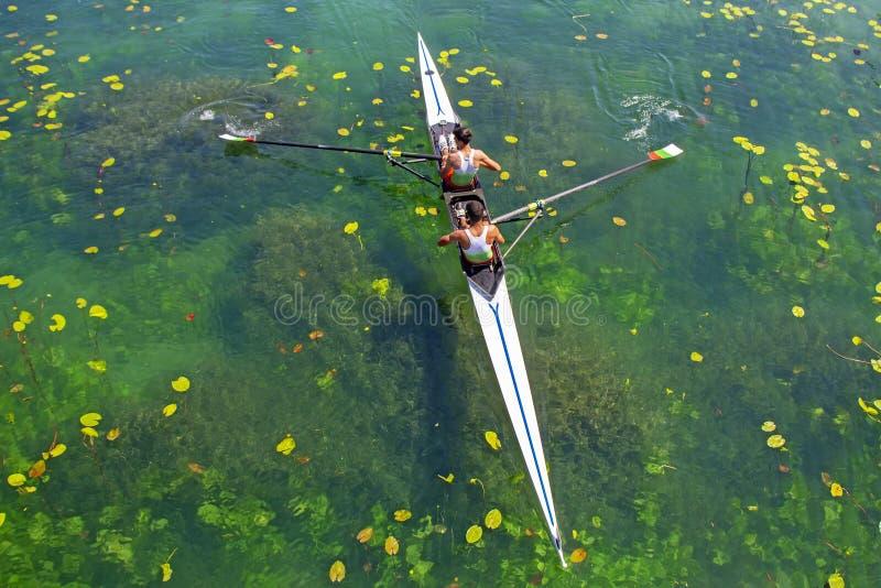 Dos jóvenes atletas remo en el lago verde fotos de archivo