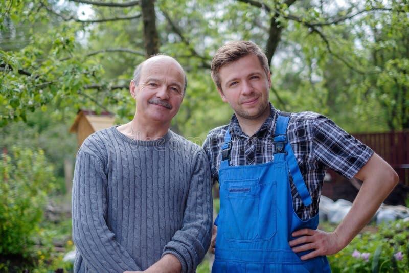 Dos jardineros felices entre los árboles verdes fotografía de archivo